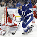 Tampa Bay Lightning center Tyler Johnson (9) goes after the puck in front of Carolina Hurricanes defenseman John-Michael Liles (26), goalie Cam Ward, and defenseman Tim Gleason (6) during the second period of an NHL hockey game Thursday, Dec. 11, 2014, in