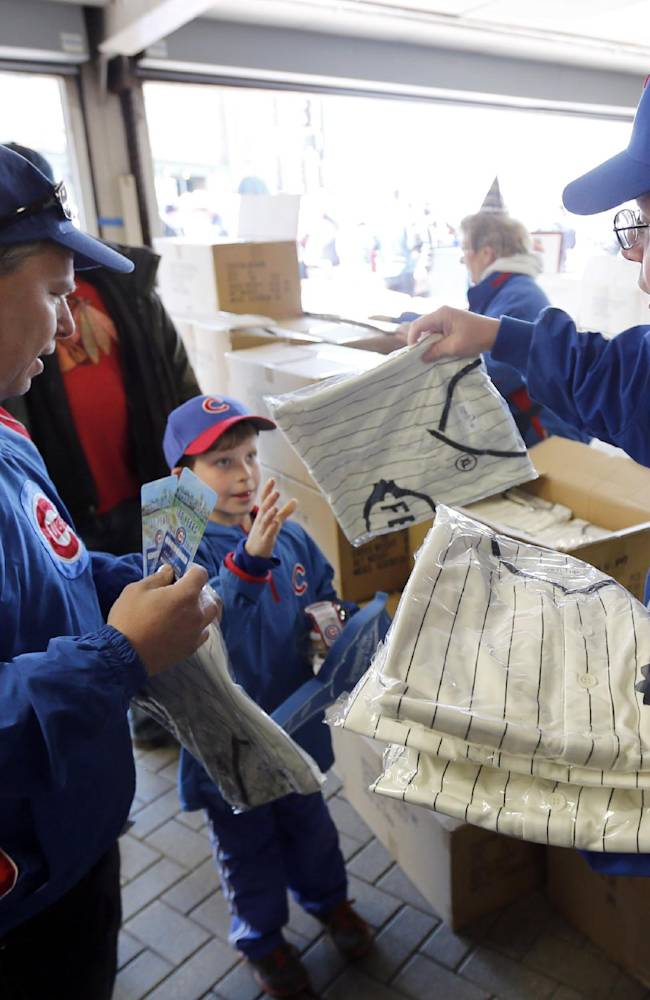 Usher John O'Brien, right, hands out the 1914 replica Chicago Federals' jersey to fans for the 100th anniversary of the first baseball game at Wrigley Field, before a game between the Arizona Diamondbacks and Chicago Cubs,  Wednesday, April 23, 2014, in Chicago