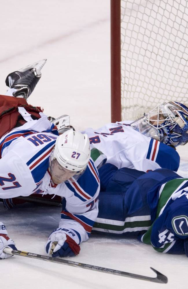 New York Rangers defenseman Ryan McDonagh (27) and Vancouver Canucks center Jordan Schroeder (45) fall over Rangers goalie Henrik Lundqvist during the second period of an NHL hockey game Tuesday, April 1, 2014, in Vancouver, British Columbia