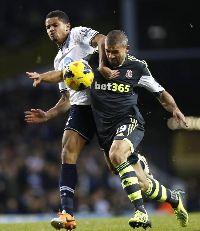 Tottenham Hotspur's Zeki Fryers, left, tussles with Stoke City's Jonathan Walters during their English Premier League soccer match at White Hart Lane, London, Sunday, Dec. 29, 2013