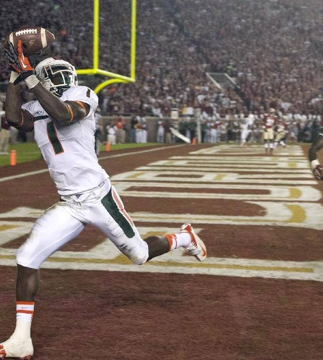 Miami wide receiver Allen Hurns (1) pulls in a 14-yard touchdown reception after getting past Florida State defensive back Jalen Ramsey (13) and linebacker Telvin Smith (22) during the second quarter of an NCAA college football game Saturday, Nov. 2, 2013, in Tallahassee, Fla