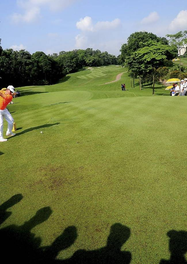 Lee Westwood, left, of England prepares to tee off on the first hole during the third round of the Malaysian Open golf tournament at Kuala Lumpur Golf and Country Club in Kuala Lumpur, Malaysia, Saturday, April 19, 2014
