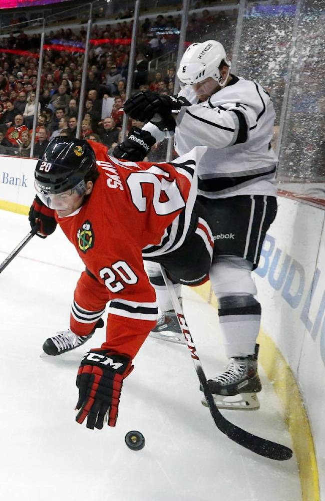 Los Angeles Kings defenseman Jake Muzzin, right, pushes Chicago Blackhawks left wing Brandon Saad (20) to the ice during the second period of an NHL hockey game Monday, Dec. 30, 2013, in Chicago