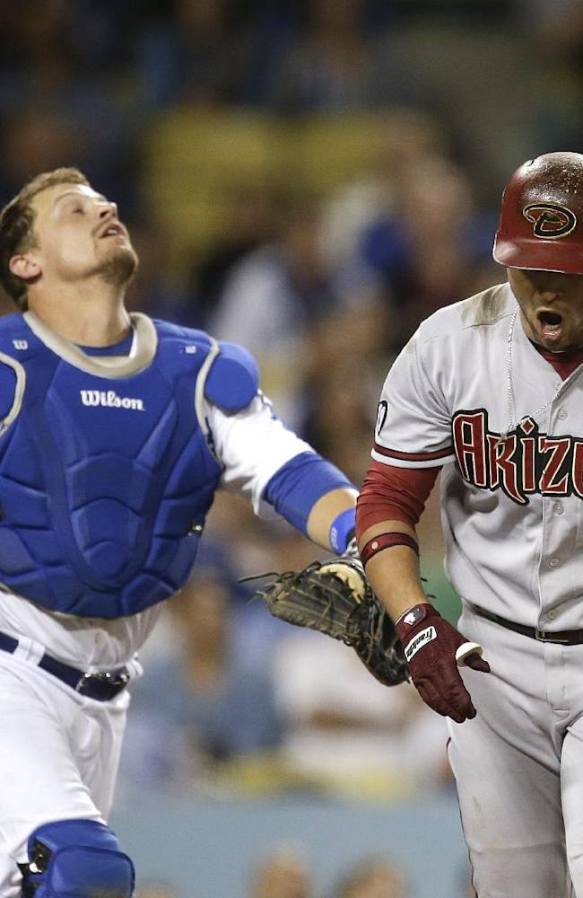 Arizona Diamondbacks' Martin Prado, right, shouts after hitting a foul ball as Los Angeles Dodgers catcher Tim Federowicz chases the ball during the seventh inning a baseball game on Monday, Sept. 9, 2013, in Los Angeles
