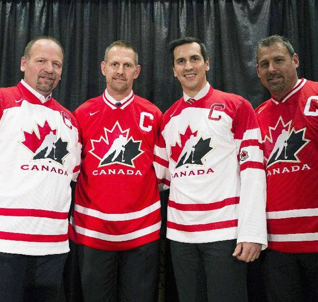 Team Canada honorary captains, from left, Wendel Clark, Gary Roberts, Marc Dennis and Martin Lapointe pose for a photograph with the official Team Canada jersey during the start of world juniors selection camp in Toronto on Friday, Dec. 13, 2013