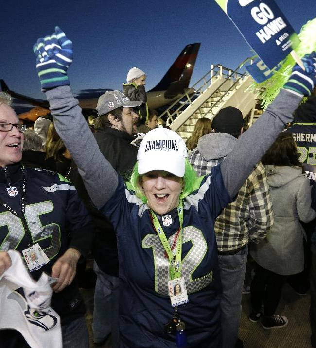 Fans start a cheer as they wait to greet Seattle Seahawks players and coaches on the team's arrival Monday, Feb. 3, 2014, at Seattle-Tacoma International Airport in Seattle. The Seahawks beat the Denver Broncos 43-8 in the Super Bowl on Sunday
