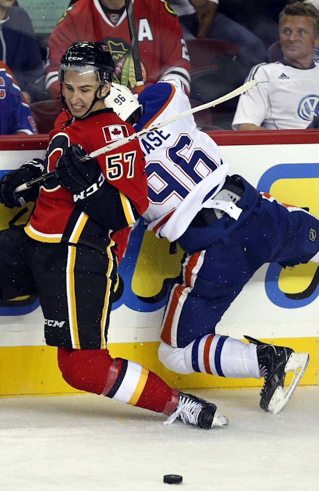 Edmonton Oilers' Gregory Chase, right, misses a check on Calgary Flames' Emile Poirier during second-period NHL preseason hockey game action in Calgary, Alberta, Saturday, Sept. 14, 2013