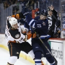 Anaheim Ducks' Ryan Getzlaf (15) and Winnipeg Jets' Adam Lowry (17) fight for the puck along the boards during the second period of their NHL hockey game in Winnipeg, Manitoba, Canada on Saturday, Dec. 13, 2014 The Associated Press