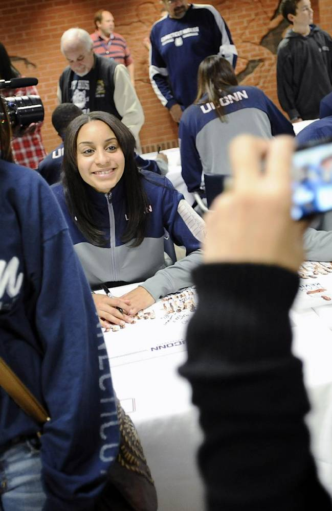 Dionna Dorsey, left, poses for a photograph with Connecticut's Bria Hartley, seated at rear, during the autograph session at the men's and women's basketball teams' First Night event Friday, Oct. 18, 2013, in Storrs, Conn