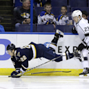 St. Louis Blues' Kevin Shattenkirk, left, is sent flying while chasing after a loose puck along side Los Angeles Kings' Dustin Brown during the second period of an NHL hockey game Tuesday, Dec. 16, 2014, in St. Louis The Associated Press