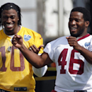 Washington Redskins quarterback Robert Griffin III, left, and running back Alfred Morris share a laugh as they walk out for practice at the team's NFL football training facility, Friday, July 25, 2014, in Richmond, Va. (AP Photo) The Associated Press