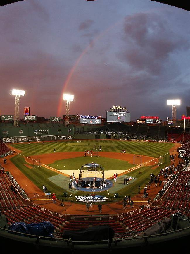 AP10ThingsToSee - In this image taken with a fisheye lens, Boston Red Sox players take batting practice as a rainbow appears in the sky above Fenway Park Tuesday, Oct. 22, 2013, in Boston. The Red Sox are scheduled to host the St. Louis Cardinals in Game 1 of baseball's World Series on Wednesday