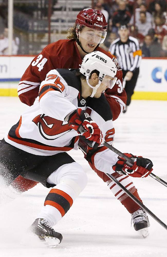 New Jersey Devils' Patrik Elias (26), of the Czech Republic, gets a pass off as he is hit by Phoenix Coyotes' Tim Kennedy (34) during the first period of an NHL hockey game on Saturday, Jan. 18, 2014, in Glendale, Ariz