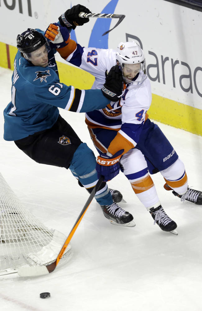 New York Islanders' Andrew MacDonald (47) collides with San Jose Sharks' Justin Braun (61) during the second period of an NHL hockey game on Tuesday, Dec. 10, 2013, in San Jose, Calif