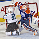 San Jose Sharks Scott Hannan (27) crashes into the net as Edmonton Oilers goalie Ben Scrivens (30) moves out of the way during second period NHL hockey action in Edmonton, Alberta, on Tuesday March 25, 2014 The Associated Press