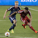 Toronto FC's Gilberto Sousa, right, battles for the ball with Chicago Fire's Jeff Larentowicz during the second half of a soccer game, Saturday, Aug. 23, 2014 in Toronto The Associated Press