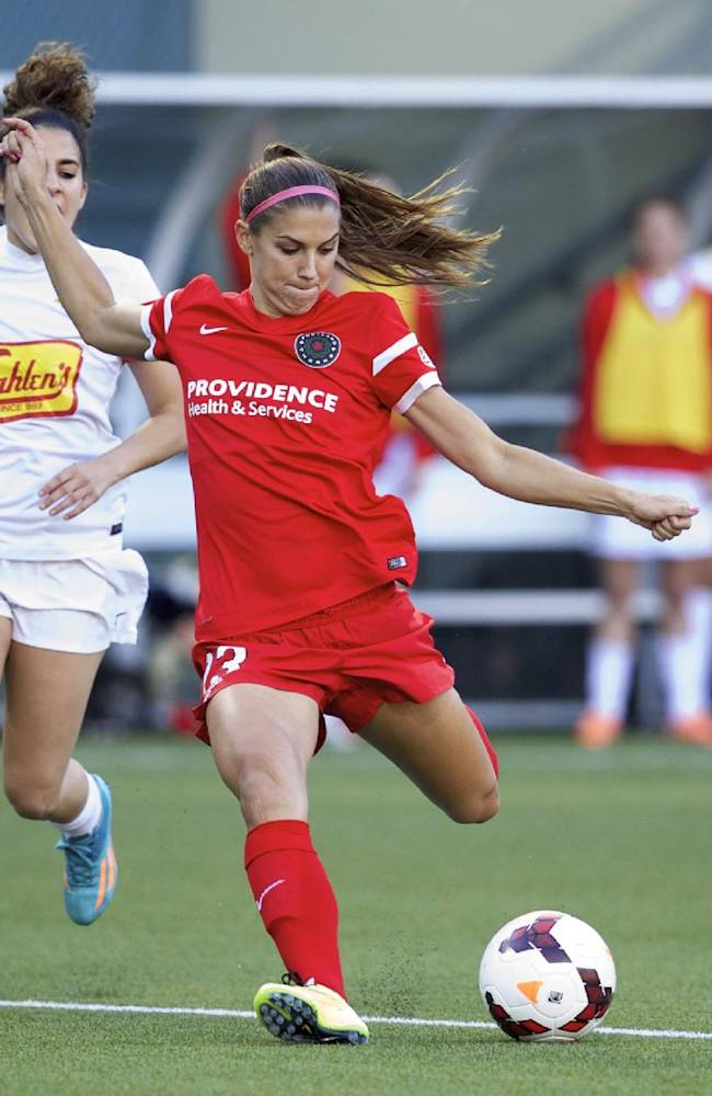 In this June 7, 2014, file photo, Portland Thorns' Alex Morgan (13) prepares to fire a shot against the Western New York Flash in an NWSL soccer game in Portland, Ore. In the space of about a week, a group of players from the U.S. team, including Morgan, wrapped up the regular season with their National Women's Soccer League teams, got together for an international friendly against Switzerland, and now face off in the NWSL playoffs