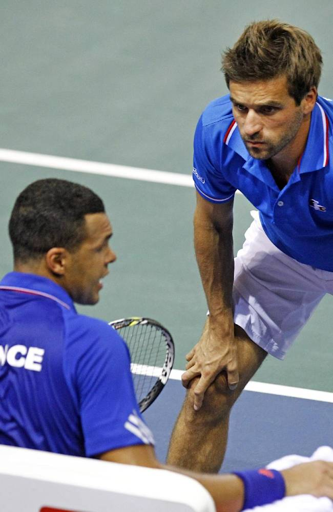 French tennis player Jo-Wifried Tsonga, left, listens to the advice of French team coach Arnaud Clement, during his single match against German player Peter Gojowczyk, in the quarterfinals of the Davis Cup in Nancy, eastern France, Friday April 4, 2014