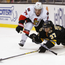 Boston Bruins' Patrice Bergeron (37) tries to poke the puck away from Ottawa Senators' Mark Borowiecki during the second period of an NHL hockey game in Boston Saturday, Dec. 13, 2014 The Associated Press