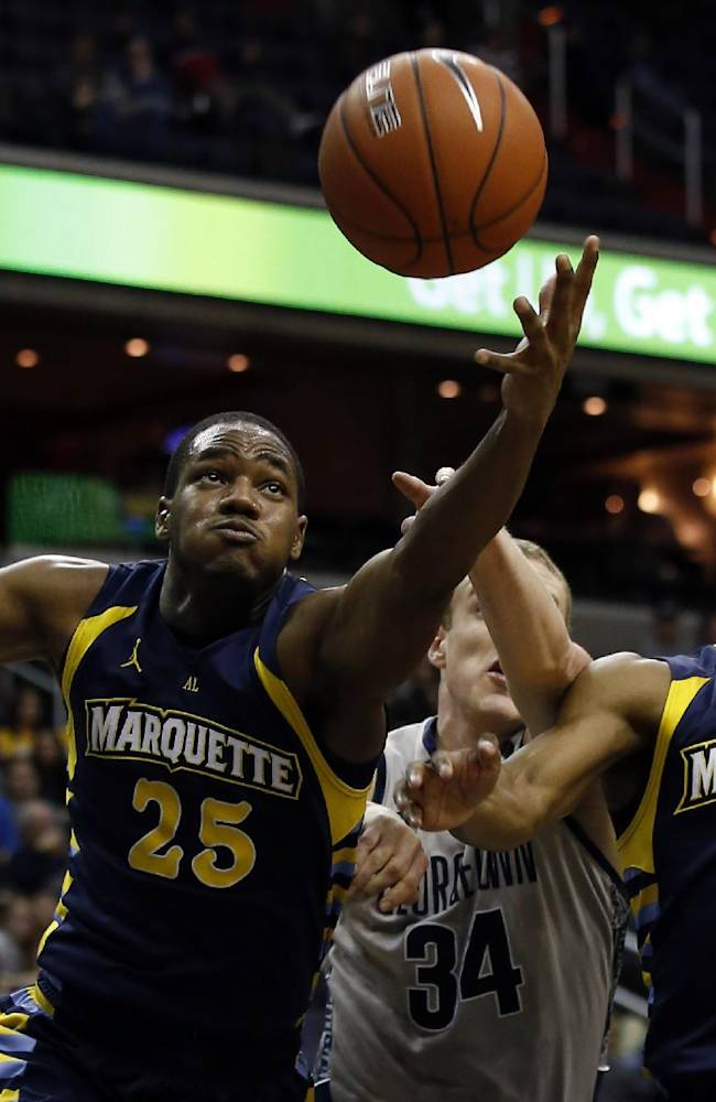Marquette forward Steve Taylor, Jr. (25) grabs a rebound in front of Georgetown forward Nate Lubick (34) and guard John Dawson (2) during the second half of an NCAA college basketball game, Monday, Jan. 20, 2014, in Washington. Marquette won 80-72 in overtime