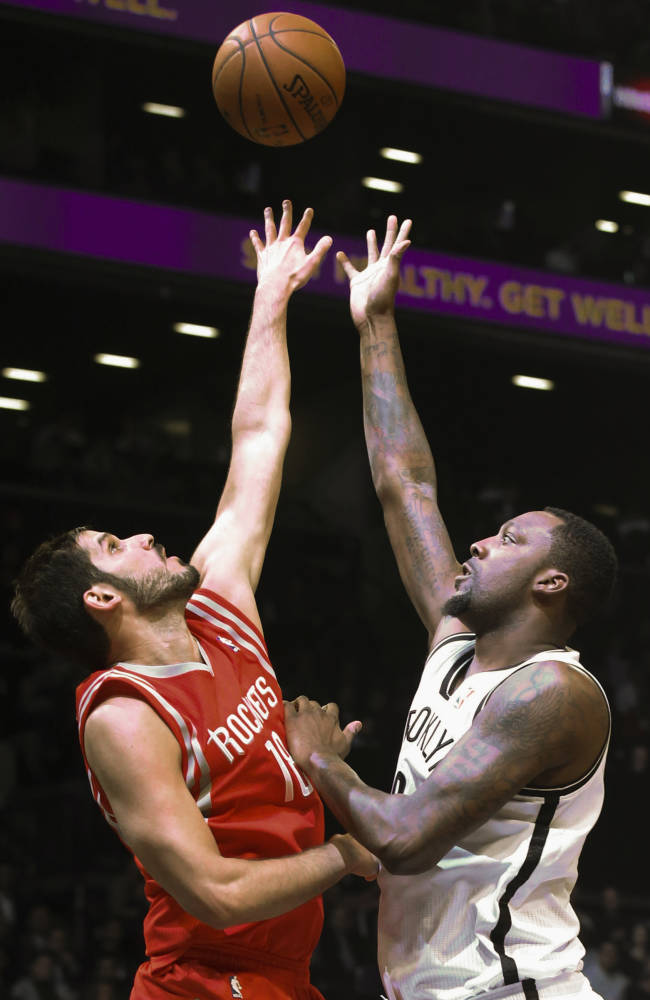 Brooklyn Nets center Andray Blatche (0), right, shoots against Houston Rockets forward Omri Casspi (18) during the first half of their NBA basketball game at the Barclays Center, Tuesday, April 1, 2014, in New York
