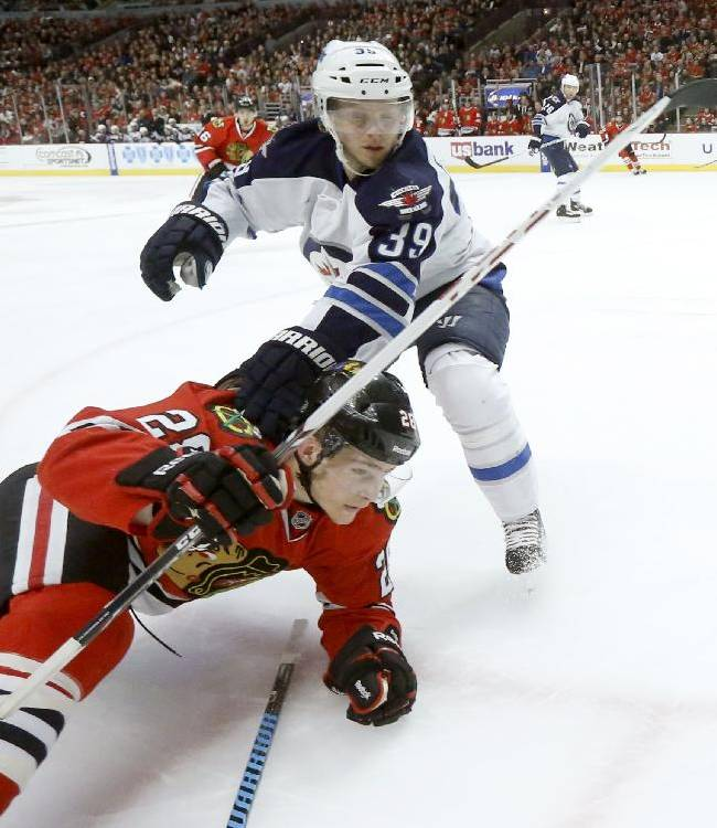 Winnipeg Jets defenseman Tobias Enstrom (39) trips Chicago Blackhawks right wing Ben Smith during the second period of an NHL hockey game Sunday, Jan. 26, 2014, in Chicago
