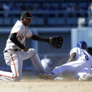 Los Angeles Dodgers' Dee Gordon, right, steals second base as San Francisco Giants shortstop Joaquin Arias misses the throw during the sixth inning of a baseball game on Friday, April 4, 2014, in Los Angeles The Associated Press