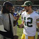 Injured Chicago Bears cornerback Charles Tillman (33) laughs with Green Bay Packers quarterback Aaron Rodgers (12) after an NFL football game Sunday, Sept. 28, 2014, in Chicago. The Packers won 38-17. The Associated Press