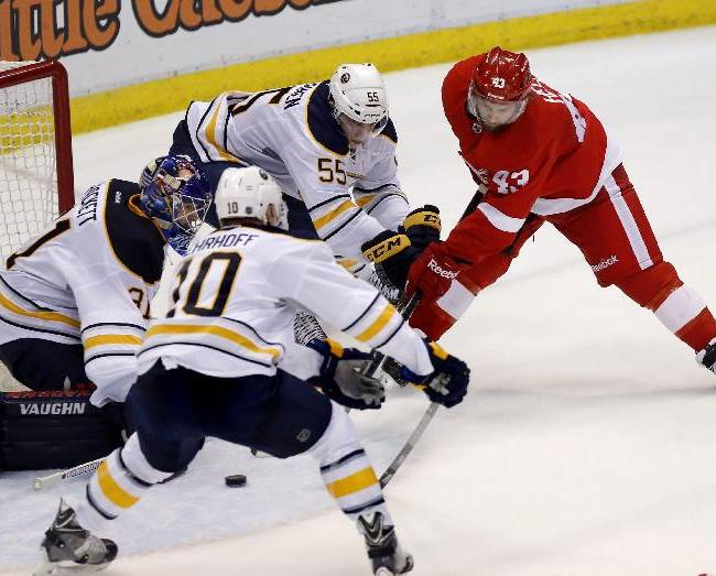 Buffalo Sabres goalie Matt Hackett, left, Christian Ehrhoff (10), of Germany, and Rasmus Ristolainen (55), of Finland, defend the goal from a shot by Detroit Red Wings' Darren Helm (43) during the third period of an NHL hockey game Friday, April 4, 2014, in Detroit. The Red Wings defeated the Sabres 3-2