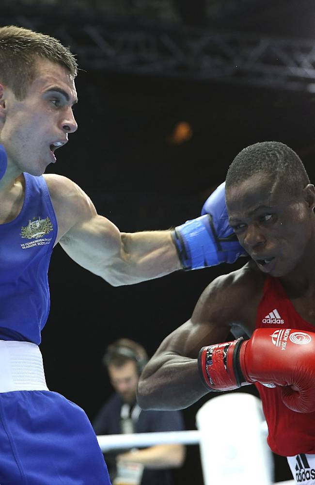 Australia's Andrew Moloney, left, lands a left hook on Nigeria's Wasiu Taiwo during their men's flyweight boxing preliminary match at the Commonwealth Games Glasgow 2014, in Scotland, Sunday, July 27, 2014