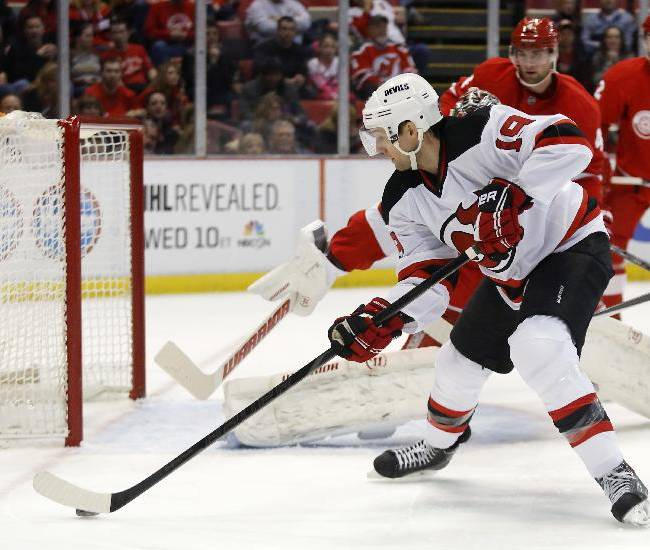 New Jersey Devils' Travis Zajac (19) takes a shot on goal against the Detroit Red Wings during the first period of an NHL hockey game Friday, March 7, 2014, in Detroit