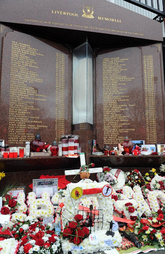 Tributes are laid at the memorial of the Hillsborough disaster outside Anfield before the English Premier League soccer match between Liverpool and Manchester City at Anfield in Liverpool, England, Sunday, April 13, 2014