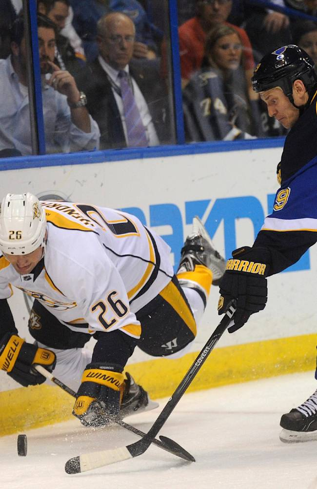 St. Louis Blues' Jay Bouwmeester (19) reaches for the puck with Nashville Predators' Matt Hendricks (26) during the first period of an NHL hockey game Thursday, Oct. 3, 2013, in St. Louis