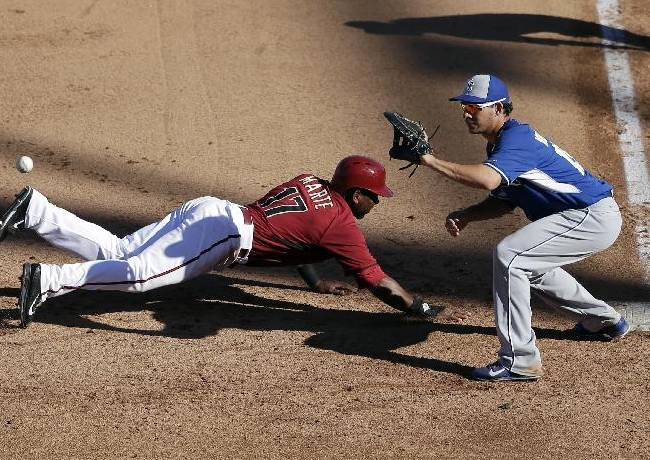 Arizona Diamondbacks' Alfredo Marte, left, gets back safely to first as Kansas City Royals first baseman Danny Valencia awaits the throw during the eighth inning of an exhibition spring training baseball game Wednesday, March 5, 2014, in Scottsdale, Ariz