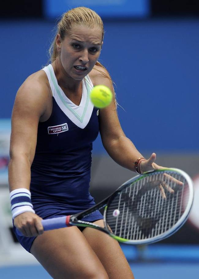 Dominika Cibulkova of Slovakia  makes a backhand return to Carla Suarez Navarro of Spain during their third round match at the Australian Open tennis championship in Melbourne, Australia, Saturday, Jan. 18, 2014