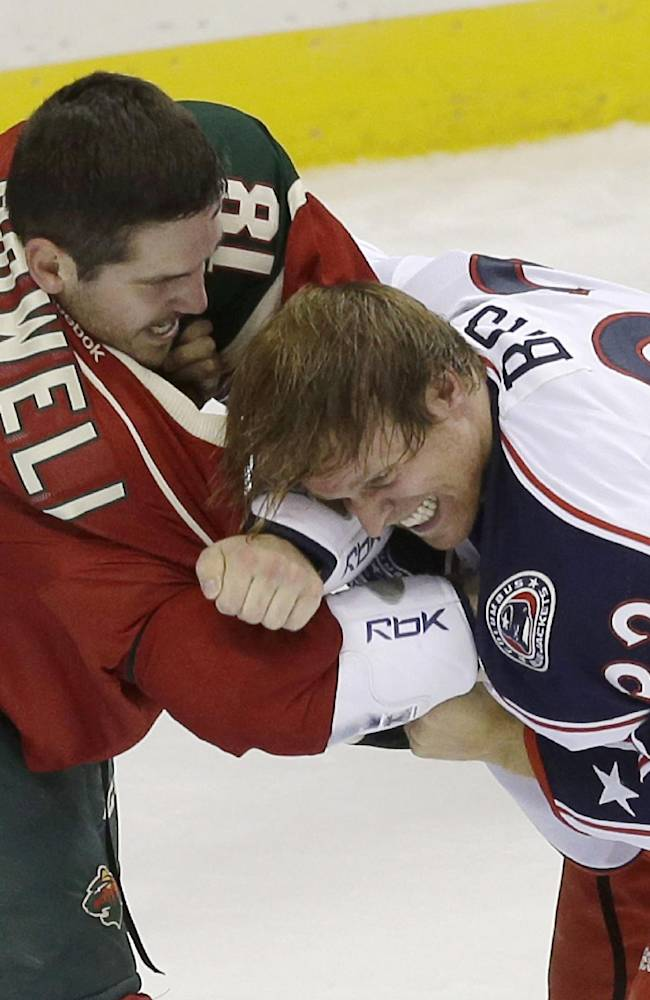 Minnesota Wild's Jake Dowell, left, and Columbus Blue Jackets' Cody Bass fight in the first period of a NHL preseason hockey game, Tuesday, Sept. 17, 2013 in St. Paul. Minn. Both received five-minute fighting penalties