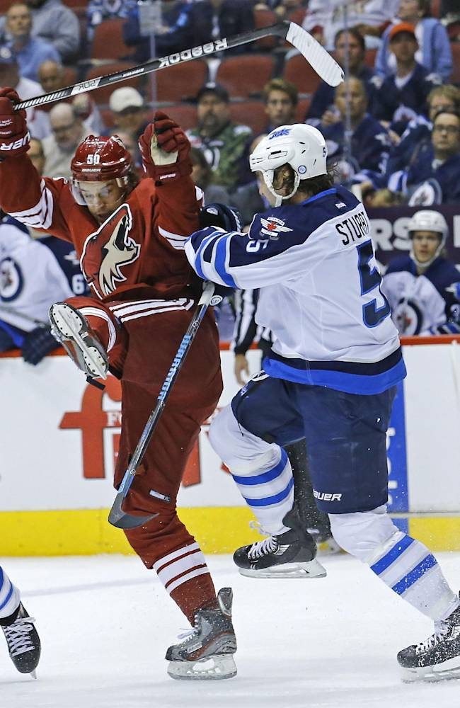 Phoenix Coyotes center Antoine Vermette (50) collides with Winnipeg Jets defenseman Mark Stuart (5) during the first period of an NHL hockey game Tuesday, April 1, 2014, in Glendale, Ariz