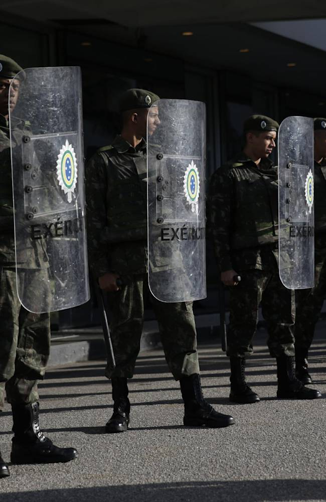 Members of the Brazilian army stand lined up before the England national soccer team arrived in their coach from the airport at the squad's hotel for the 2014 soccer World Cup in Rio do Janeiro, Brazil, Sunday, June 8, 2014