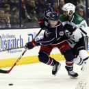 Columbus Blue Jackets' Matt Calvert, left, works for the puck against Dallas Stars' Jordie Benn during the second period of an NHL hockey game in Columbus, Ohio, Tuesday, Oct. 14, 2014 The Associated Press
