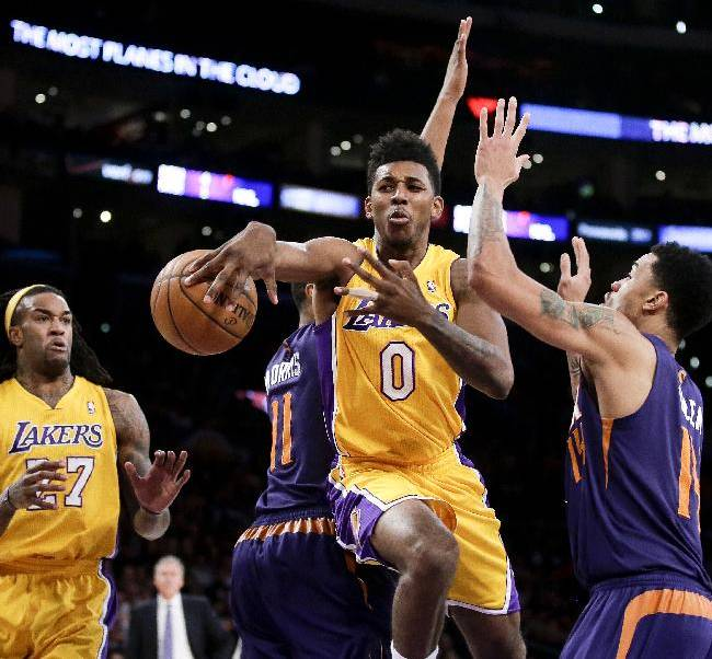 Los Angeles Lakers forward Nick Young, middle, passes to Jordan Hill, left, between Phoenix Suns guard Gerald Green, right, and Markieff Morris during the first half of an NBA basketball game in Los Angeles, Tuesday, Dec. 10, 2013