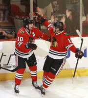 Chicago Blackhawks' Patrick Sharp, left, and Jeremy Morin (11) celebrate after Sharp's goal in the second period of an NHL hockey game against the St. Louis Blues in Chicago on Sunday, April 6, 2014. (AP Photo/Charles Cherney)
