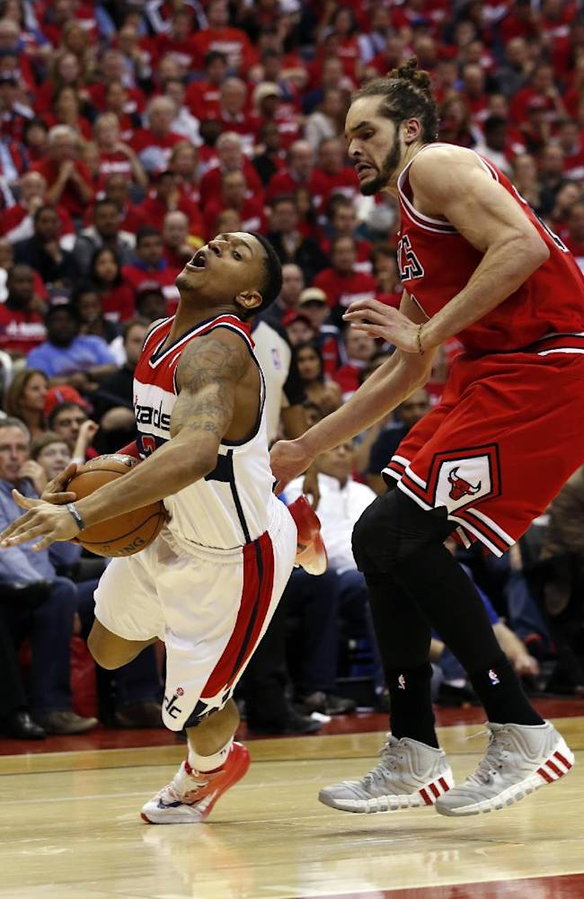 Washington Wizards guard John Wall (2) falls with Chicago Bulls center Joakim Noah (13) defending in the second half of Game 3 of an opening-round NBA basketball playoff series on Friday, April 25, 2014, in Washington. The Bulls won 100-97