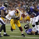 Washington Redskins wide receiver Santana Moss, center, scores a touchdown between Baltimore Ravens defenders Darian Stewart, left, John Simon, bottom right, and Terrence Brooks in the second half of an NFL preseason football game, Saturday, Aug. 23, 2014