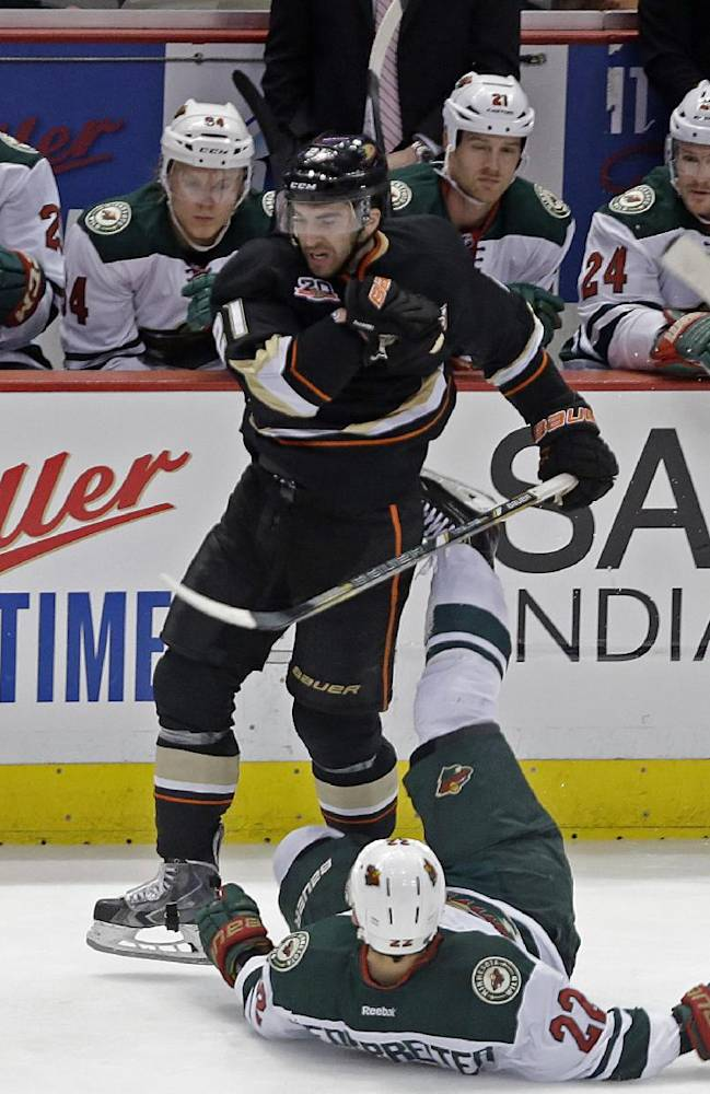Anaheim Ducks right winger Kyle Palmieri (21) and Minnesota Wild right winger Nino Niederreiter (22), of Switzerland, tangle in front of the Wild bench in the first period of an NHL hockey game in Anaheim, Calif.,Tuesday, Jan. 28, 2014. The Wild won, 4-2