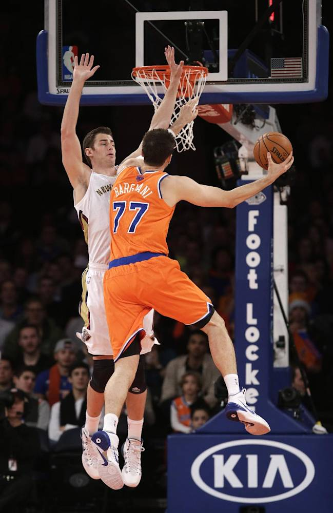 New Orleans Pelicans forward Ryan Anderson (33) defends as New York Knicks forward Andrea Bargnani (77) of Italy goes up for a layup in the first half of their NBA basketball game at Madison Square Garden in New York, Sunday, Dec. 1, 2013
