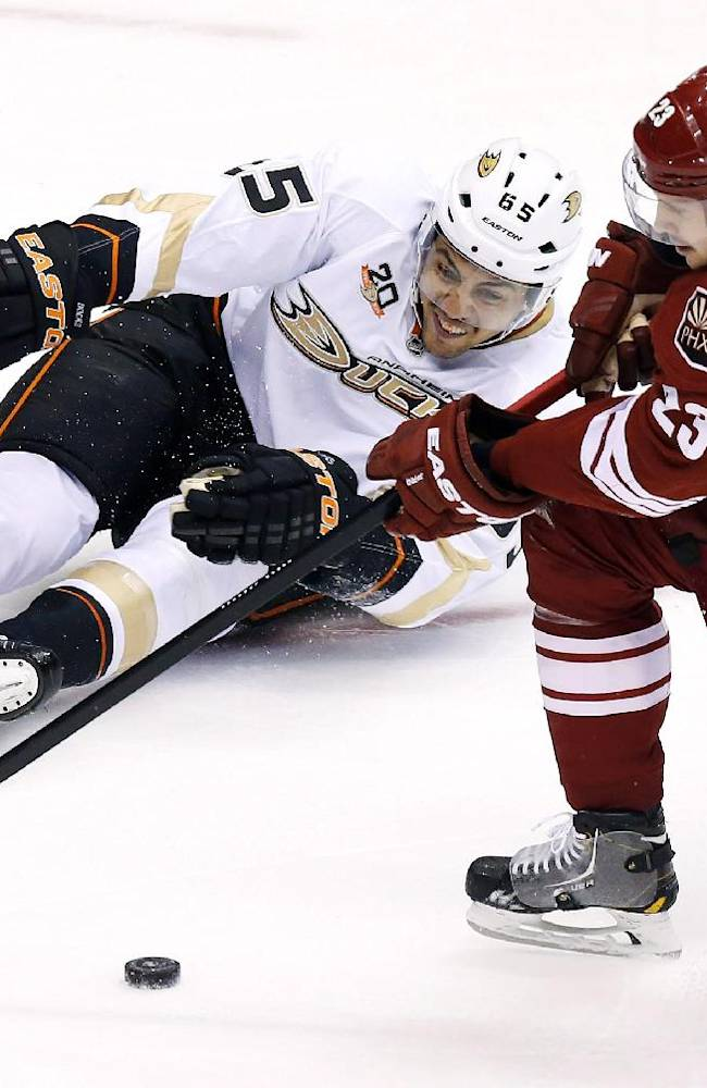 Anaheim Ducks' Emerson Etem, left, tries to get his stick on the puck as Phoenix Coyotes' Oliver Ekman-Larsson (23), of Sweden, arrives to take control of the puck during the first period of an NHL hockey game Saturday, Nov. 23, 2013, in Glendale, Ariz