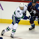 Vancouver Canucks defenseman Christopher Tanev, left, looks for a pass as Colorado Avalanche center Ryan O'Reilly covers in the second period of an NHL hockey game in Denver on Tuesday, Nov. 4, 2014 The Associated Press