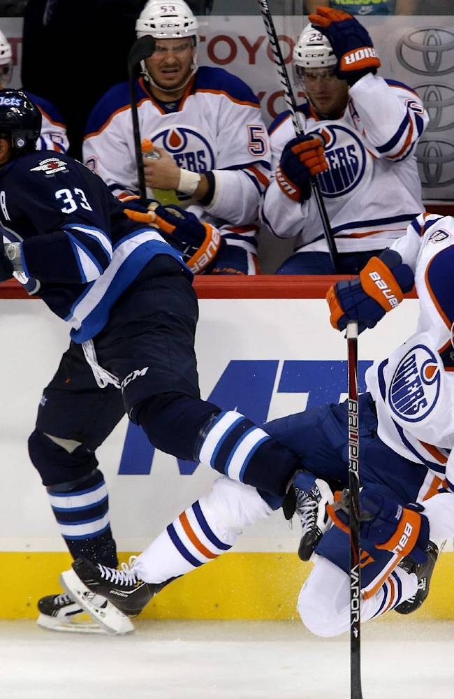Winnipeg Jets' Dustin Byfuglien (33) collides with Edmonton Oilers' Jesse Joensuu (6) during the third period of a preseason NHL hockey game in Winnipeg, Manitoba, Tuesday, Sept. 17, 2013