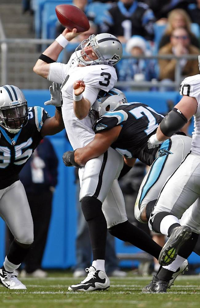 In this Dec. 23, 2012 file photo, Oakland Raiders' Carson Palmer (3) is hit by Carolina Panthers' Greg Hardy (76) and Charles Johnson (95) while throwing a pass during the first half of an NFL football game in Charlotte, N.C. Hardy, a.k.a. the
