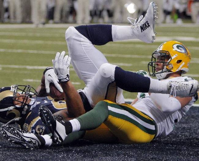 St. Louis Rams tight end Lance Kendricks, left, lands in the end zone after catching an 11-yard touchdown pass as Green Bay Packers cornerback Micah Hyde defends during the second quarter of a preseason NFL football game Saturday, Aug. 16, 2014, in St. Louis